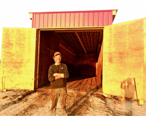 Conan Eaton in front of the world's first documented aerated in-vessel compost heat recovery system at Auburn Star Farm in Lunenburg, Vermont.